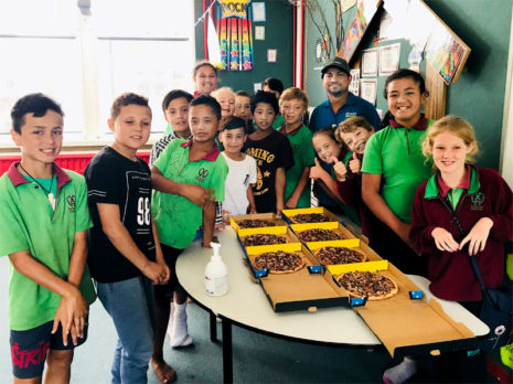 Smithesh Thomas hands out pizza to youngsters at Somerset Crescent School, Palmerston North.