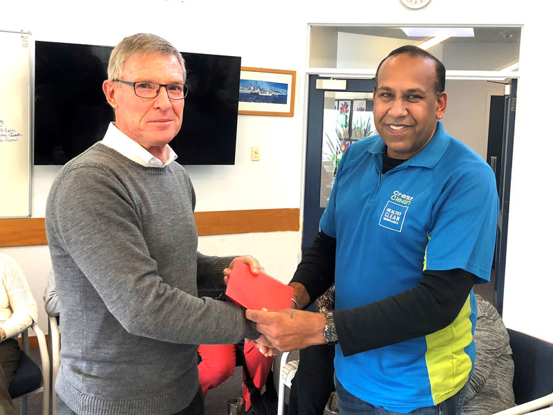 Brian Bayly, Macleans Primary School principal, presents a card and gift voucher to CrestClean's Kamal Jeet Singh.