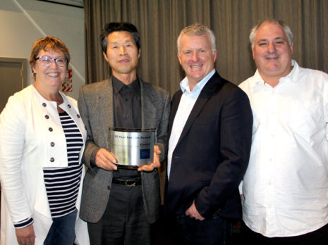 Martin Kim receives his 15-year long service award from CrestClean managing director Grant McLauchlan. Looking on are Caroline Wedding, Auckland West regional manager, and Dries Mangnus, Auckland Central regional manager.