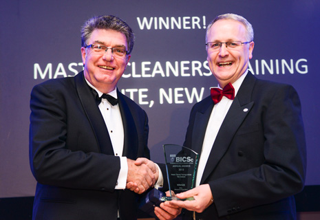 Pictured is Adam Hodge, CEO of Master Cleaners Training Institute receiving the prestigious international trophy for Outstanding Performance in Promotion of the Institute from Colin Hanks, BICSc's International General Manager.