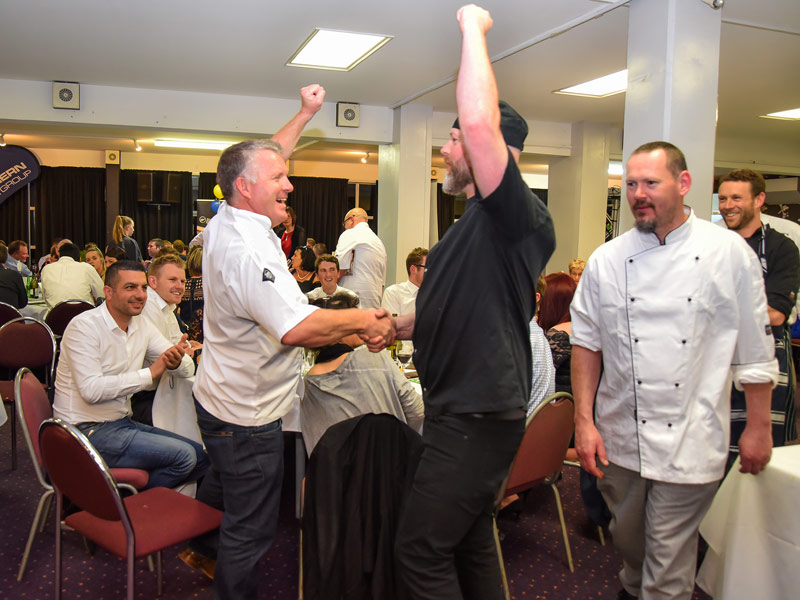 Grant shares a jubilant moment with celebrity chef Andy Aiken at the big night in Dunedin.