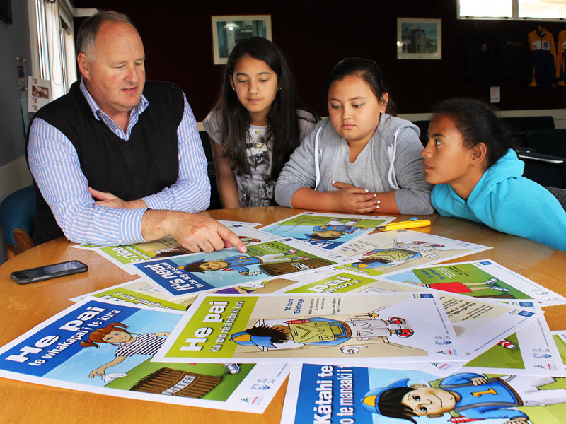 Principal Peter Barker shows the new posters to pupils Leah Walker, Jade Nelson and Crystal Mihaka-Barrett.