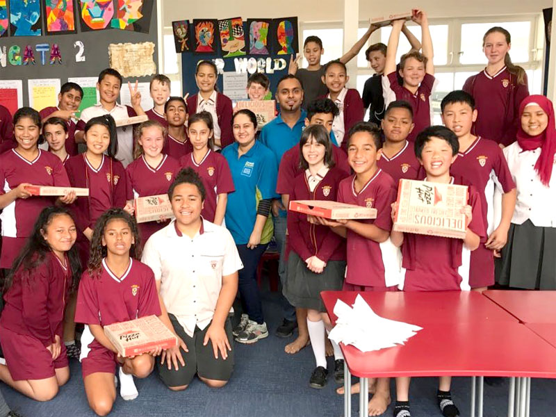 Ajneel and Bhartika Singh hand out pizza to Room 17 students at Howick intermediate School for winning the Cleanest Classroom Award.