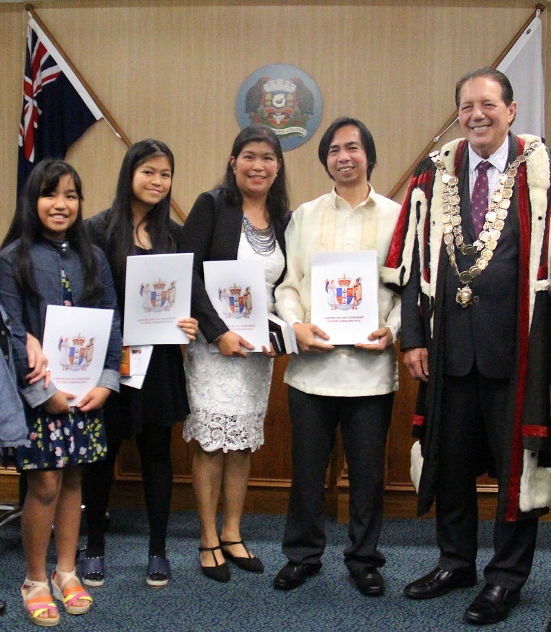 The family receive their New Zealand Citizenship Certificates from Invercargill Mayor Tim Shadbolt. Photo: Invercargill City Council