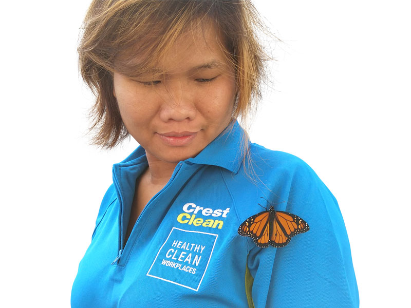 Zar San enjoys the moment as a monarch butterfly briefly rests on her CrestClean uniform.