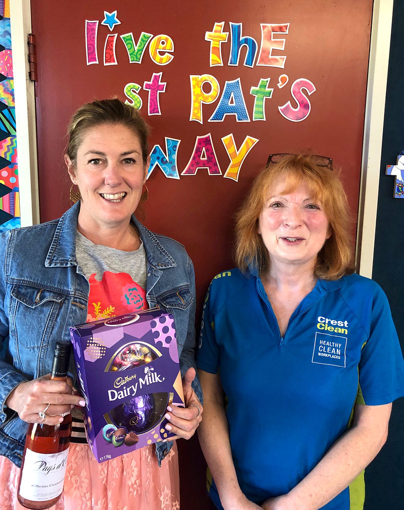 Teacher Kaehlah Dawson is delighted to receive a surprise gift of choclotes and wine from CrestClean business owner Deborah Herries.