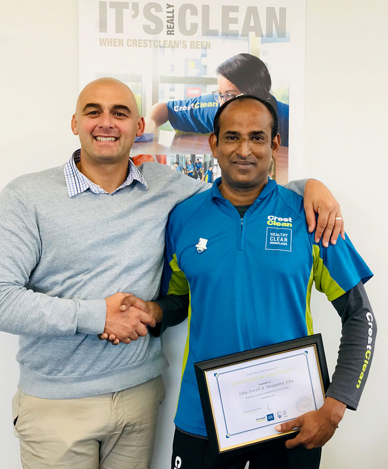 Joby Joseph receives his long service award from Tony Kramers, CrestClean's Dunedin Regional Manager.