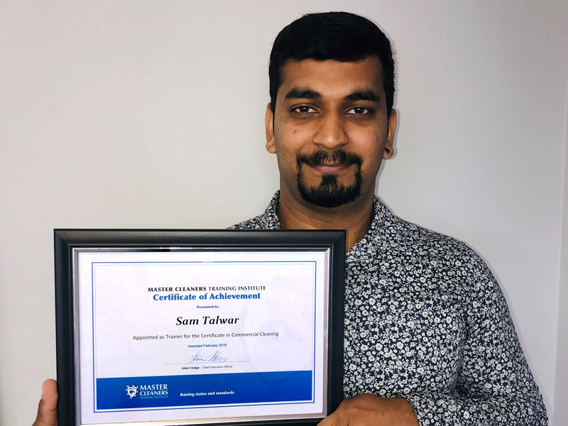 Sam Talwar with his certificate from Master Cleaners Training Institute.