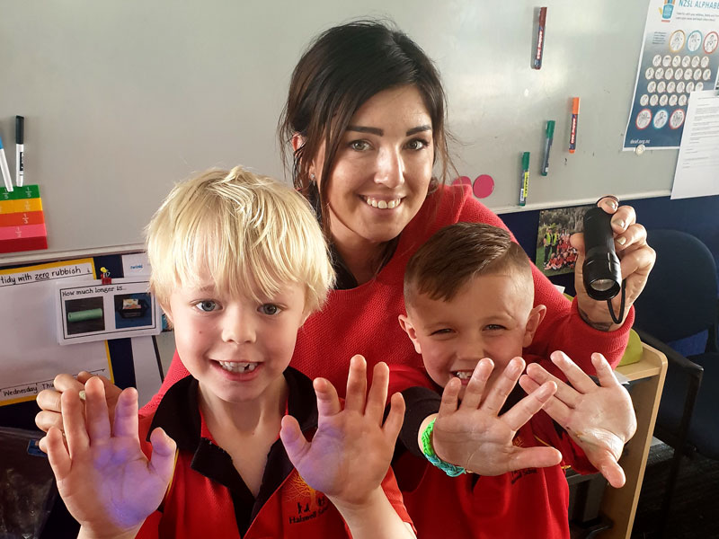 "Two youngsters check for ""invisible germs"" on their hands during a session on hand-hygiene presented by Gina Holland."